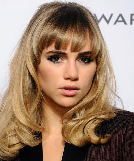 The best celebrity bangs for heart-shaped faces: Suki Waterhouse channels Godard's French New Wave heroines with eye-framing arched bangs. The longer strands on the sides help de-emphasize a narrow chin.