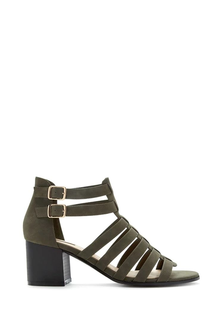 A pair of open-toe faux suede heels featuring a caged cutout design, a double buckled ankle, and a chunky block heel.
