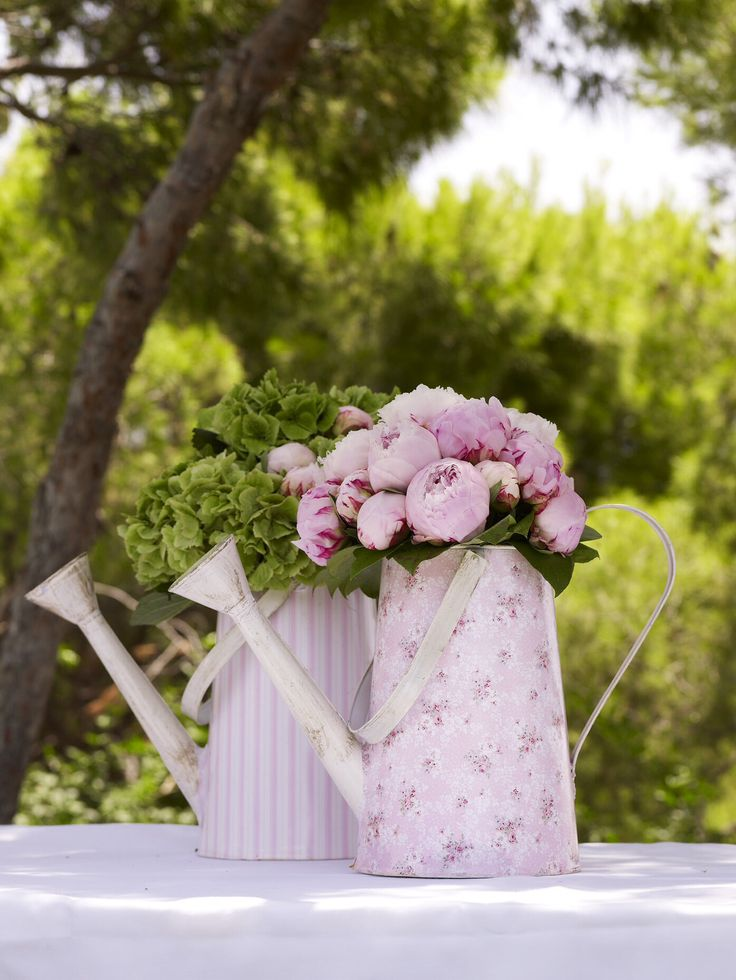 Painted Watering cans used as vases for these beautiful peonies and hydrangeas.  http://www.instyle.gr/photo-gallery/roz-vaftisi-koritsiou/