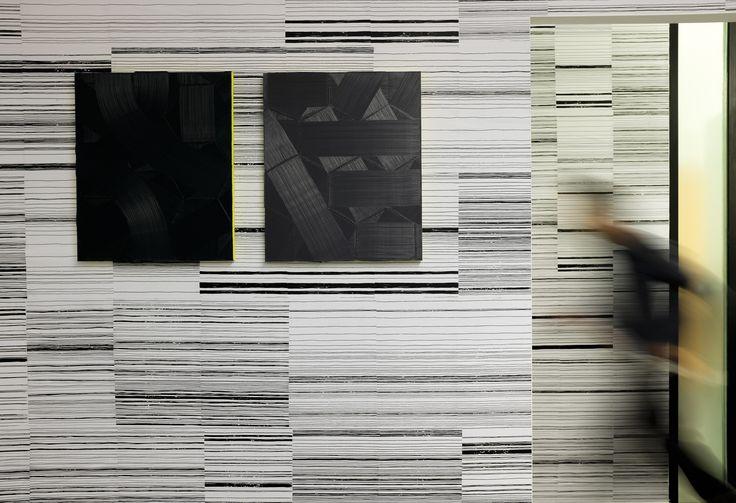 """Lo spazio rettangolare è definito dalle pareti personalizzate dall'artista pescarese Rashid Uri con il suo lavoro Astratto geometrico, """"...un numero infinito di linee tracciate a mano libera su carta fanno da sfondo ai due monocromi dipinti ad olio in altrettante variazioni di grigio. Trentasei disegni sono fotocopiati ed installati secondo un ordine preciso generando un testo. Un idioma astratto la cui punteggiatura è data dalla pittura ...""""."""