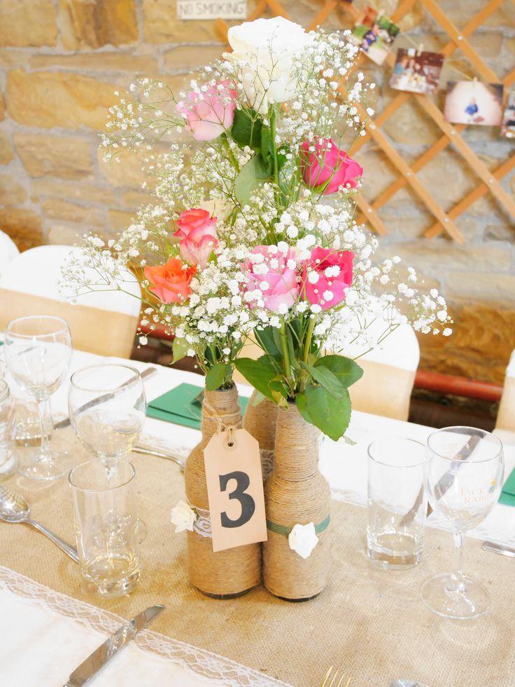 Homemade burlap table runner, twine bottles, and table numbers. DIY flowers. Rustic wedding.