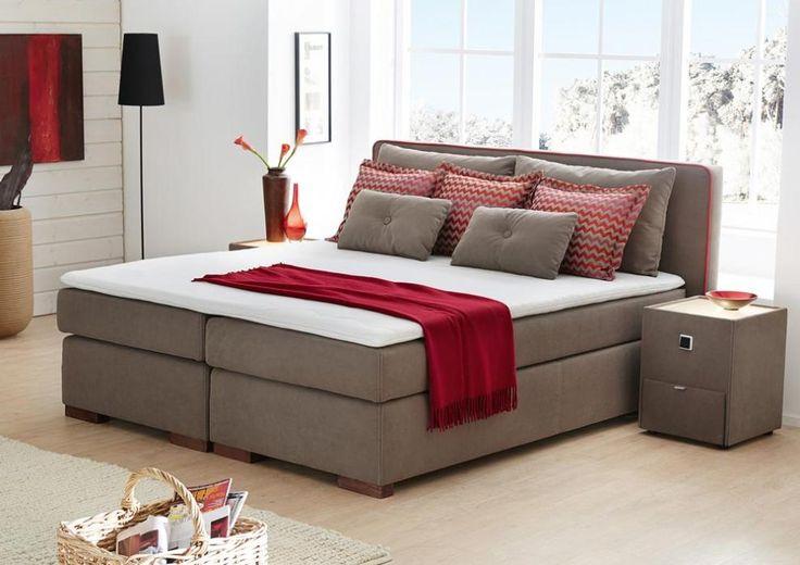 So schön können Boxspringbetten sein! Das stilvolle graue Bett harmoniert perfekt mit den sparsam eingesetzten roten Akzenten.