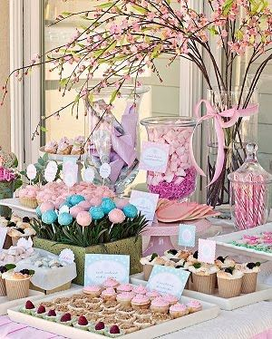 Candy buffet with tall floral arrangements and different glass and apothecary jars.