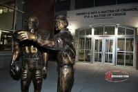 A magnificent statue of Tom Osborne with a Nebraska football player greets fans near the main entrance of the Osborne Complex.