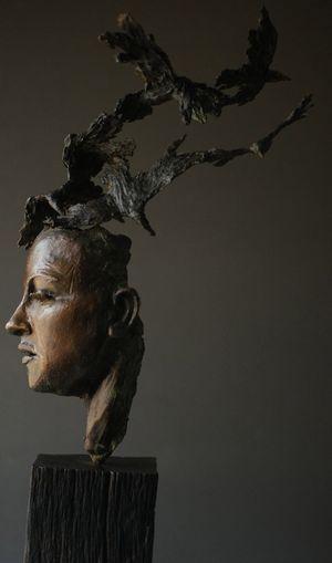 """'Philip Wakeham: """"La chica de las sombras"""".  escultura de bronce. (Cara con cuervos)."""