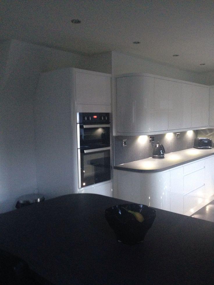 White gloss handless wren kitchen, grey slate work top and floor, built in double oven