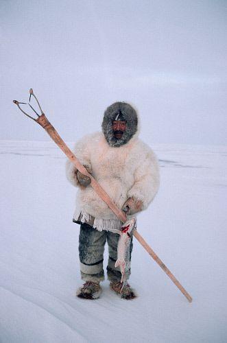 Aipilik, an Inuk hunter in fox furs with Kakivak (Inuit fish spear) & fish. Igloolik, Nunavut, Canada © Bryan & Cherry Alexander Photography