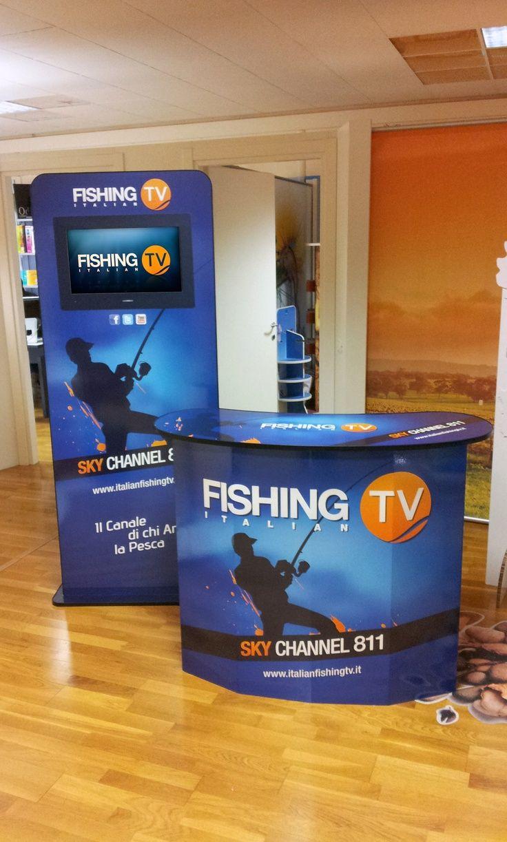 """Isola Promozionale """"Fishing Tv"""" con Totem Multimediale personalizzato con grafica uv fotorealistica, e completo di Display 22"""" Full Hd e Media Player. La struttura si completa di Desk Promoter personalizzato, ed utilizzato per attività di In-store Promotion. Agenzia: Atlantide"""