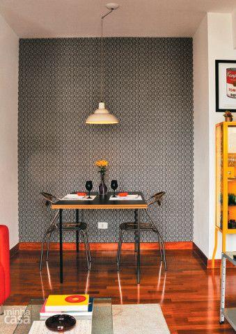 Duas chapas sobrepostas de MDF com acabamento formam o tampo da mesa. Um desviador instalado no teto centraliza o pendente sobre a mesa. A parede do fundo destaca-se por causa do papel de parede com grafismos em cinza. Projeto de Renata Carboni e Thiago Lorente.