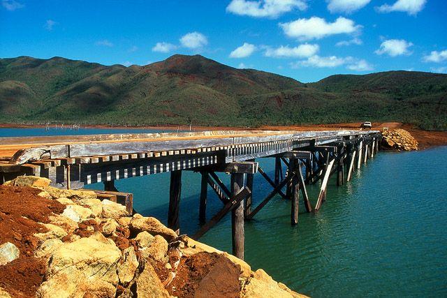 Parc de la Rivière Bleue, Pont Pérignon - Yaté - Grande Terre, Province Sud - Nouvelle-Calédonie Le Pont Pérignon a été édifié par M. Pérignon, exploitant forestier, juste avant le remplissage du barrage de Yaté en 1958. Ce pont, présentant un tablier de 83 m en planches, repose sur une charpente en chêne-gomme (Arillastrum gummiferum, imputrescible) et en tamanou (Calophyllum inophyllum, Bintagor). Fragilisé lors du passage du cyclone Erica, le Pont Pérignon se traverse exclusivement à…