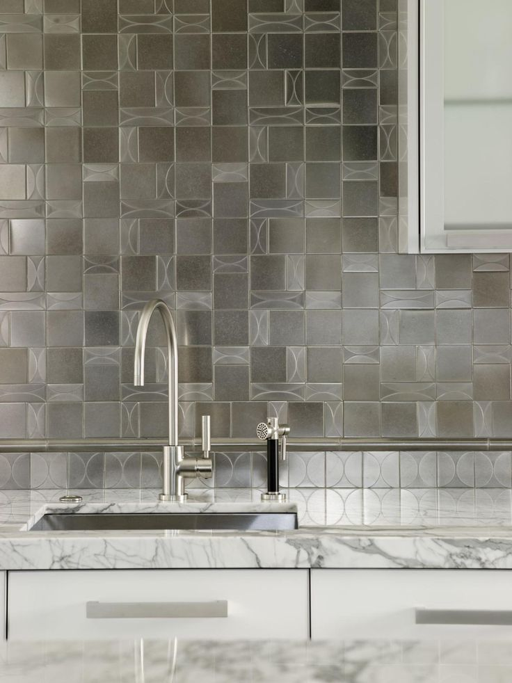 geometric tile backsplash marble counter in modern white kitchen by