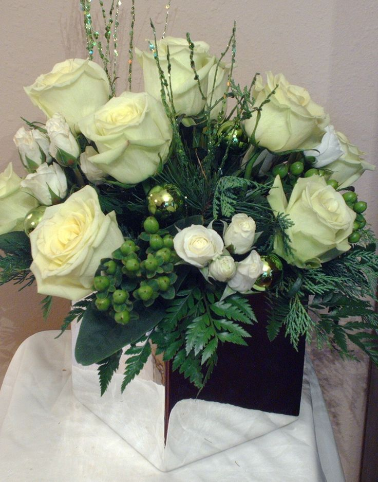 Holiday Centerpieces using a silver cube vase with white and green accents and flowers