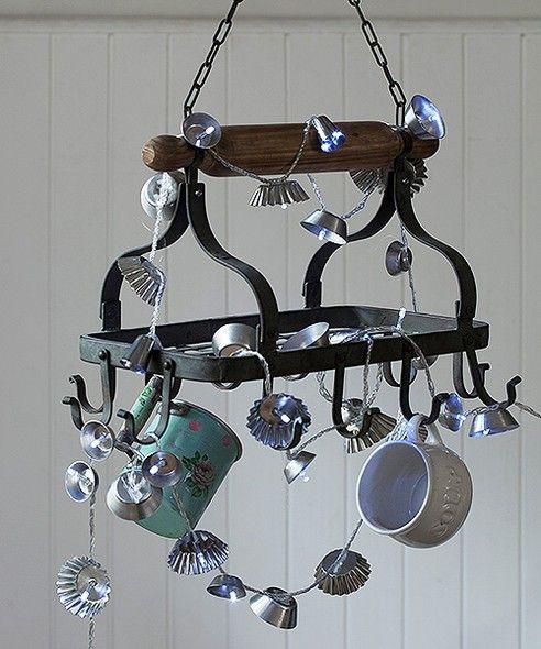 Para uma iluminação criativa para a cozinha, fure forminhas com um prego, encaixe as luzes e dê o arremate com cola quente. Pendurado num paneleiro rústico, o pisca-pisca vira um perfeito lustre. Paneleiro Villa Pano, utensílios la Calle Florida