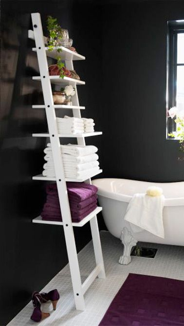 Une étagère murale en forme d'échelle, c'est une jolie idée déco dans une salle de bain qui ne permet pas d'accueillir un meuble à cause de sa petite superficie. Dans cette salle de bain aux murs couleur chocolat, l'échelle sert d'étagère pour entreposer toutes les serviettes de bain. Un rangement qui prend un minimum de place et qui embellit la déco de la pièce, que demander de plus ?