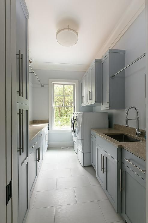 Long Gray Laundry Room Boasts A Tension Rod Drying Rack Mounted To Gray  Shaker Cabinets Fixed