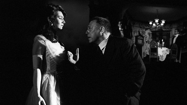 Photo from a stage production of An Inspector Calls with Inspector Goole interrogating Sheila Birling