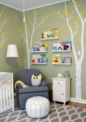 Gender-Neutral Nursery — Green Walls, White Birch Trees with Yellow Leaves — Wall Decals — Grey Birds — Art Shelves for Children's Books — Grey Glider Rocker — White Leather Moroccan Ottoman with Grey Stitching — Owl Pillow — Grey and White flat weave rug carpet — Shana Cunningham Designs