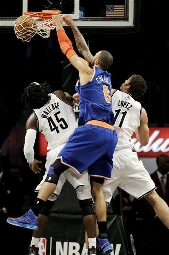 New York Knicks center Tyson Chandler (6) dunks over Brooklyn Nets forward Gerald Wallace (45) and center Brook Lopez (11) in the first half