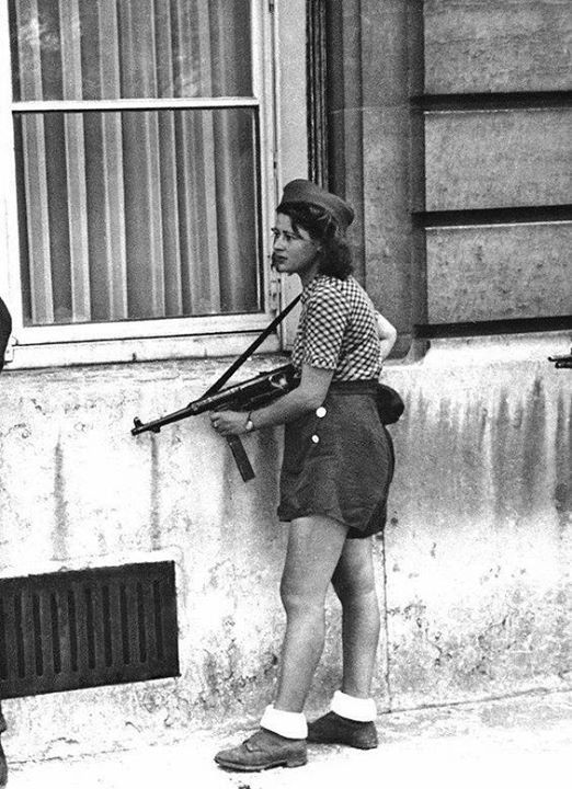 A women of the French resistance movement who is a member of a patrol routing out Germans snipers still left in areas of Paris France on August 29 1944.  (carrying a German Schmeisser submachinegun or MP40.)
