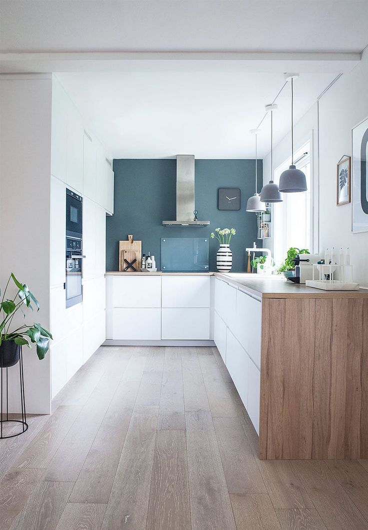 Lovely bright kitchen with a wonderful warm blue wall. The white kitchen elements and the wooden worktop are from Ikea, while the lamps above the table are from Muuto. Behind the stove a bulletin board in tempered glass is mounted to protect the wall from grease and dirt.