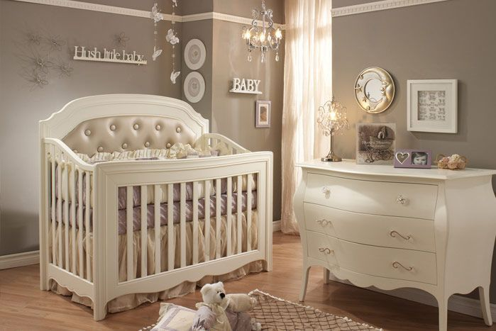 This nursery splashes neutral beige and white tones over a natural hardwood floor, with curved facade dresser standing next to large wood cr...