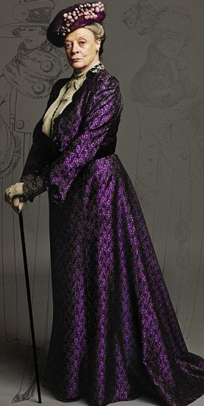 "Lady Violet, the Dowager Countess    ""This outfit was made for Maggie Smith as Violet. The fabric was created by reproducing an Edwardian print onto silk. The design was based on a jacket from the era. We used original lace for the edging and cuff detail. The blouse had a lace bow and high neck added. The hat has vintage cotton baubles covered with a fine net dyed to match the suit.""    -- costume designer Susannah Buxton"