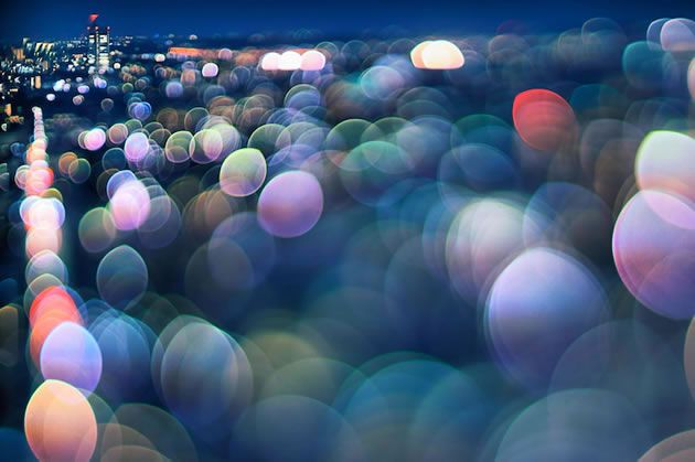 Takashi Kitajima stands on high-rise buildings and photographs Tokyo city at night, capturing radiant semi-abstract urban landscapes. This composition contains a single focused area, surrounded by circular, glowing 'bokeh' – shimmering orbs that appear when a camera lens attempts to record unfocused points of light. Bokeh is created in different ways by different lenses – typically appearing unintentionally in the background of a scene. In this image, Kitajima has used a narrow depth of ...