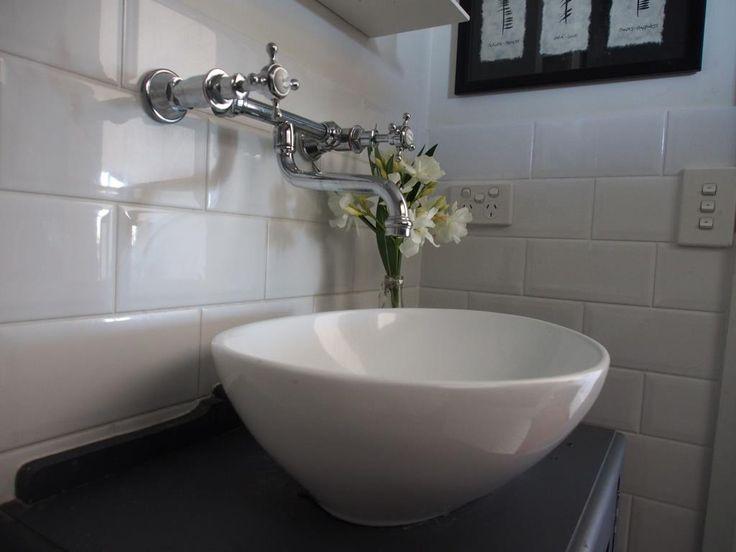 Close up beveled edge subway tiles, above mounted vanity basin, traditional wall mounted tapware.