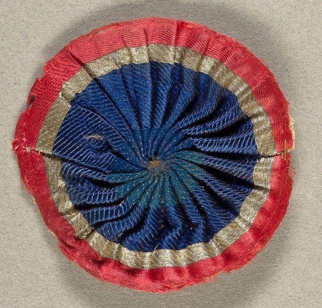 Cocarde tricolore pour chapeau, tissée en fils d'argent. En l'état. Période Révolutionnaire. Diam.: 7 cm. Vendu à l'Hôtel des ventes de Toulon