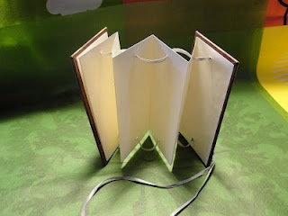 A small simple venetian blind style book with a beaded drawstring to close.