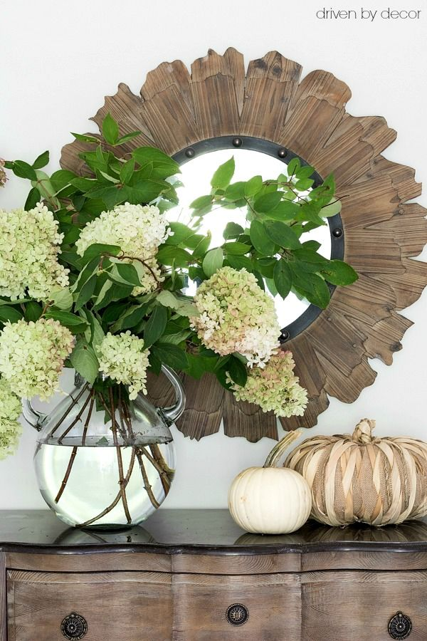 Large glass jug filled with hydrangeas as part of a simple fall vignette