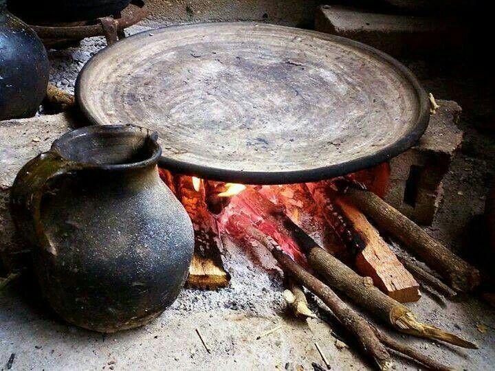 El comal de barro en la lumbre, al lado una  vasija  de barro también.