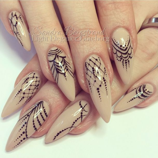 nude stiletto nail with detailed goth/lace design...