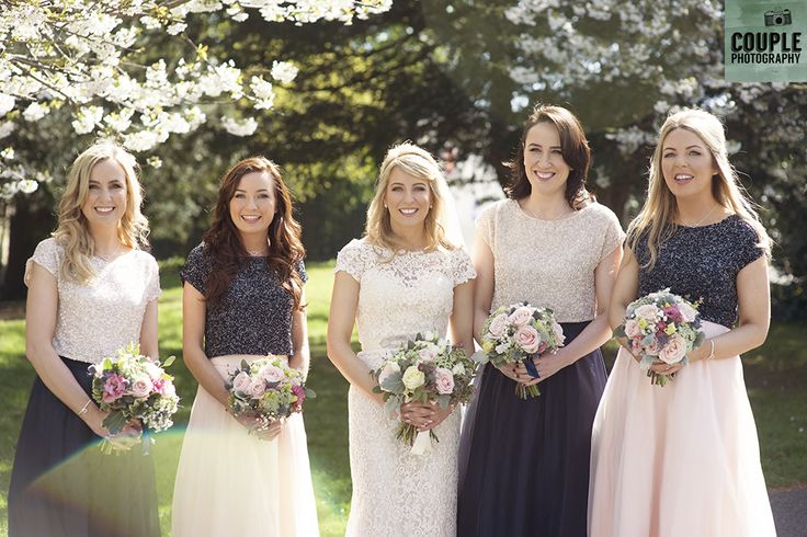 The bride & her bridesmaids in pink and navy under the white cherry blossom outside the church. Weddings at The Cliff at Lyons by Couple Photography.