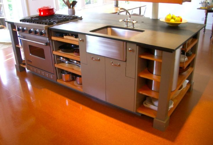 オレンジ色の床に映える、メタリックが綺麗なキッチン。オーブンレンジもついて、一つにぎゅっとまとまっています。