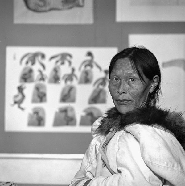 """Pitseolak Ashoona moved to Cape Dorset in the late 1950s where she taught herself to draw and was an active contributor to the annual print collection. Pitseolak standing in front of her print """"Mother Birds Protecting Eggs,"""" 1961, in the art centre at Cape Dorset, photograph by B. Korda, 1961."""