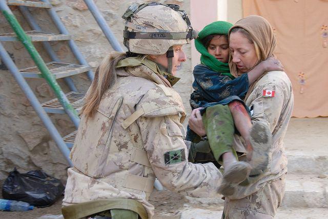 Le Caporal-chef Anouk Beaudet (à gauche) prend soin d'une jeune Afghane qui s'est brûlée, avec l'aide de la Capitaine Hélène Lescelleur, lors d'une clinique médicale gratuite composée de personnel médical et dentaire afghan, canadien et américain, dans la ville de Spin Boldak en Afghanistan. L'escadron A de 12e Régiment blindé du Canada (12 RBC) a également distribué des souliers à près de 1 000 jeunes Afghans.
