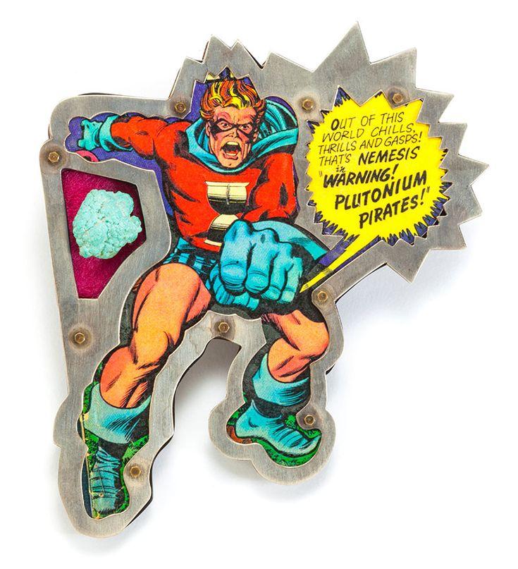 """Warning Plutonium Pirate Betsy King-Spilla, 1991 argento 925, rame, plexiglas, carta,lamina di metallo e """"plutonio"""", montata 8,89 x 10,16 x 0,63 cm Collezione privata, USA Un'immagine pittorica di un famoso supereroe dei fumetti è meticolosamente incastonata nell'argento lavorato. Il titolo della spilla rafforza l'avvertimento dell'immagine: i Pirati di Plutonio stanno per sferrare un attacco nucleare. Si tratta di un esempio di gioiello narrativo americano.Sala Arte - II Edizione 2017 - 20"""