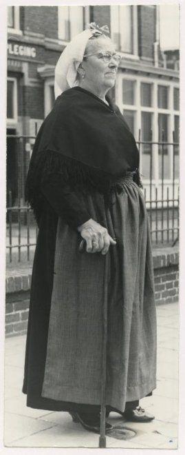 Scheveningse vrouw voor de Ziekenverpleging in de Duinstraat; zij draagt een geplooide muts, een ijzer met boeken en parelspelden; een zwarte omslagdoek, een schort (lichte rouw). 1968 Hans de Bakker #ZuidHolland #Scheveningen