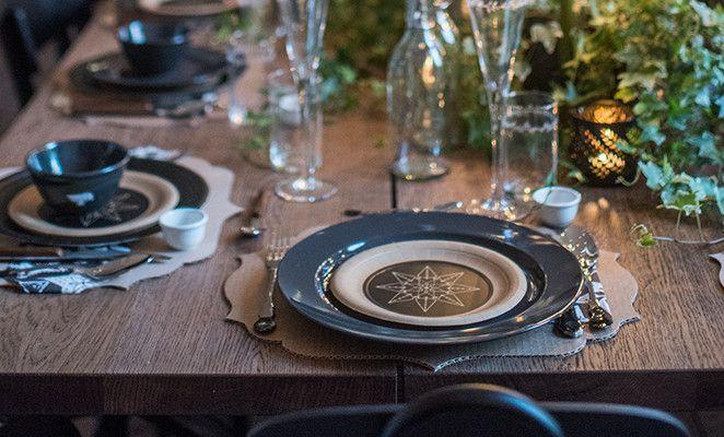 Per l'apparecchiatura della tavola è stato scelto uno stile informale nelle tonalità del nero, alternando piatti in ceramica e in carta e variando anche le posate. Per dare un tocco di creatività, le posate in acciaio sono state colorate con uno smalto nero.   Al posto della tovaglia, sono state ricavate delle tovagliette ritagliando una sagoma nel cartone. Un dettaglio basic in piena armonia con il centrotavola d'ispirazione naturale.