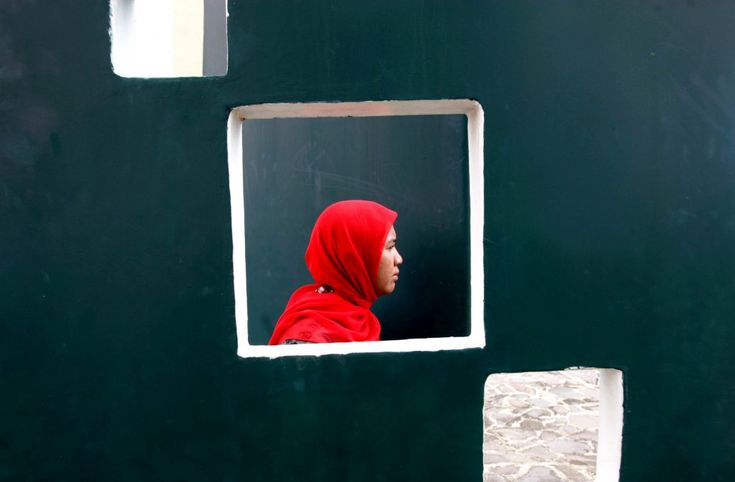 An Acehnese woman is seen through an opening on a wall as she attends a prayer commemorating the 8th anniversary of the Indian Ocean tsunami in Banda Aceh, Aceh province, Indonesia. (AP)