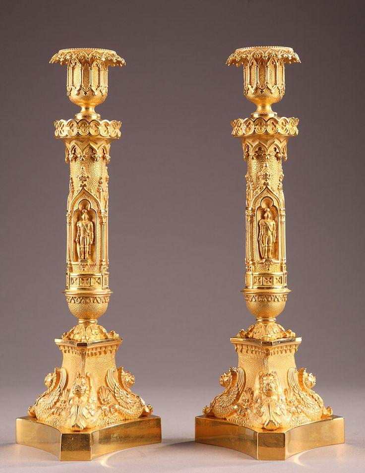 Une très belle paire de bougeoirs en bronze doré et ciselé, comportant une base trilobée sur laquelle repose des animaux ailés. Des niches dans le goût gothique qui ornent le...