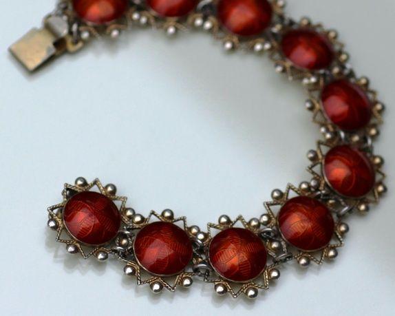 Armbånd i forgylt sølv, med rød emalje. Ti stiliserte blomster. Arne Nordlie, Oslo. Stemplet: Nordlies mestermerke, 925 S Lengde: ca. ...