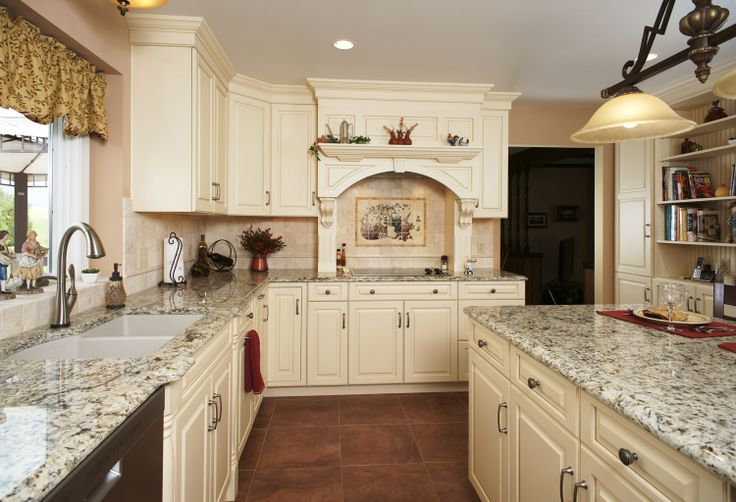 Traditional white kitchen with a hearth hood over the for Traditional white kitchen cabinets