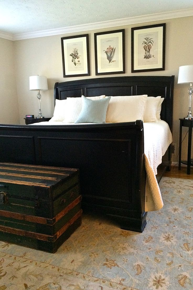 Master Bedroom with a jet black sleigh bed from @Pottery Barn. Lush super comforable white bedding and walls painted in @SherwinWilliams Stucco (SW7569). A vintage patina trunk and gorgeous light blue and tan floral carpet.