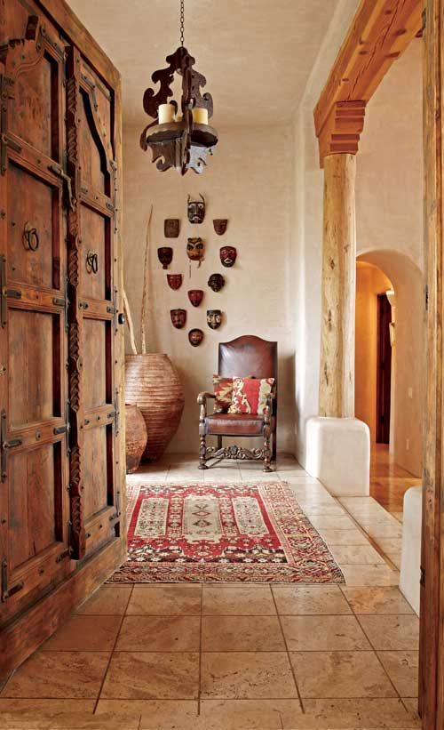 In the entry to this lovely Southwestern home, a collection of Guatemalan masks and a kilim rug add to the home's rustic authenticity. - Traditional Home® Photo: Michael Venera Design: Patty Burdick