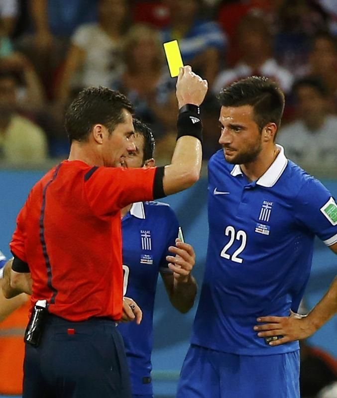 Referee Benjamin Williams of Australia shows the yellow card to Greece's Andreas Samaris (R) during their 2014 World Cup round of 16 game against Costa Rica at the Pernambuco arena in Recife June 29, 2014.