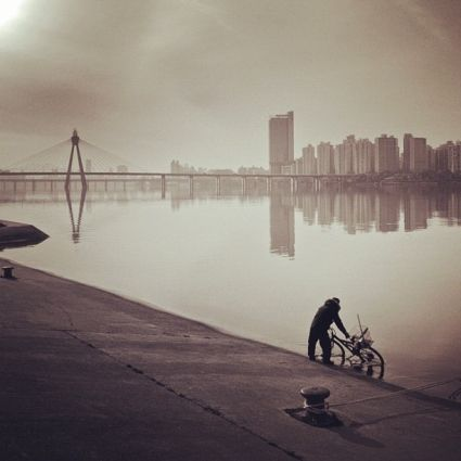 """From the best Instagram Photos Ever Taken by Amy-Mae Elliot, Mashable:  7. Philip Park (@Philip Park)    Josh Riedel: """"Millions of people live in Seoul, but this photo makes you believe there is only this one man and his bicycle."""""""