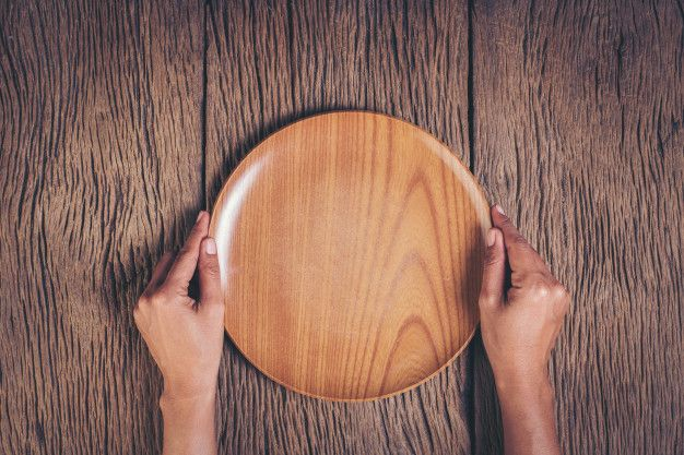 Top View Hand Holding Plate On Wood Background Free Photo