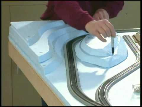 This video series, hosted by Michael Gross, will teach you the simple how-to workshop techniques you need to know to take an HO scale electric train set and make it a scenic model railroad. Well show you how to build a 4x8 model train table (benchwork) from plywood, lay sections of track, create easy realistic scenery using foam and paint, assem...